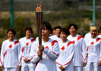 Foto di tedofori incaricati di portare la torcia olimpica a Tokyo