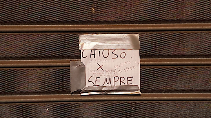 cartello sulla saracinesca di un negozio chiuso per la crisi